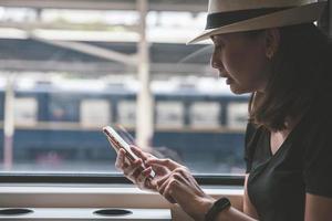 viajante linda jovem usando o smartphone em uma estação de trem, transporte e conceito de estilo de vida de viagens foto