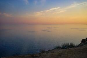 pôr do sol nublado colorido sobre um corpo de água foto