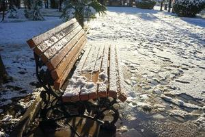 neve em um banco de madeira em um parque nevado foto