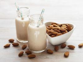 leite de amêndoa e amêndoas em uma mesa foto