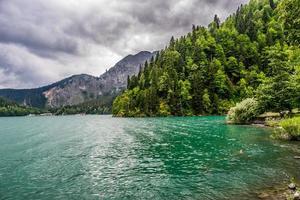 lago verde emoldurado pela floresta e montanhas com céu nublado foto