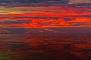 Pôr do sol nublado vermelho colorido sobre um corpo de água foto
