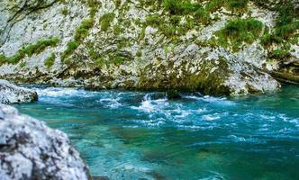 um rio correndo entre costões rochosos ao lado de uma montanha foto
