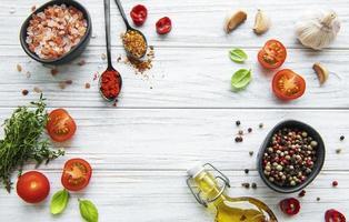 tomate, manjericão e pimenta com alho em fundo branco de madeira foto