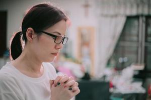 mulher asiática orando em casa. foto