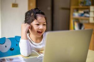 menina asiática aprendendo e estudando online com uma videochamada com um professor, garota feliz, aprendendo online com o laptop em casa. novo normal. coronavírus covid-19. distanciamento social. fique em casa