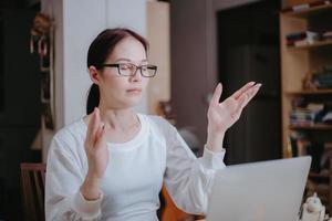 mulher asiática orando na frente do laptop, conceito online de adoração.