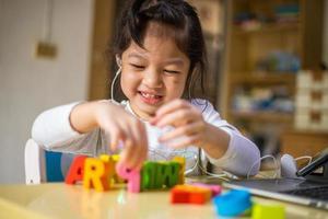 menina asiática aprendendo alfabetos online, garota feliz, aprendendo online com o laptop em casa. novo normal. coronavírus covid-19. distanciamento social. fique em casa