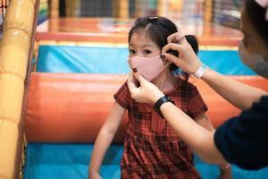 uma mãe está colocando uma máscara facial para sua filha.