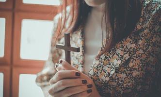 uma mulher está orando e segurando uma cruz foto