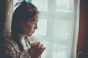 uma mulher está orando com os olhos fechados. foto