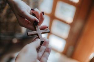 uma cruz de madeira nas mãos da mulher. foto