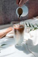 barista servindo leite em um copo de café gelado