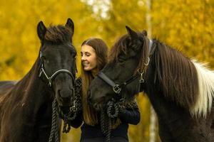jovem com seus dois cavalos islandeses foto