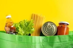 conceito de entrega de comida em um fundo amarelo. saco biodegradável com alimentos essenciais. foto