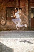 bela jovem pulando alto durante o treinamento no ambiente urbano foto