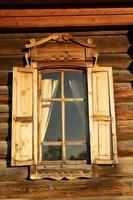 janela vintage com platibandas em uma cabana de madeira
