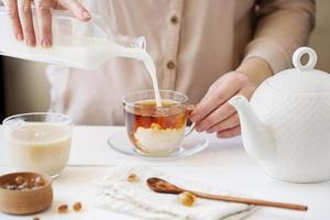 vista frontal pessoa preparando chá com leite foto