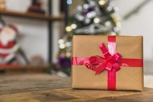 caixa de presente com fita vermelha na mesa foto