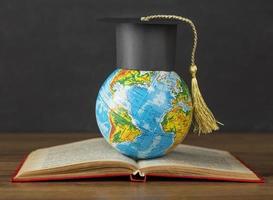 chapéu de formatura no globo terrestre e livro escolar aberto foto