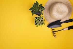 ferramentas de jardinagem com chapéu de palha e copie o espaço no fundo amarelo foto