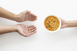 mão dando tigela de sopa para pessoa necessitada foto