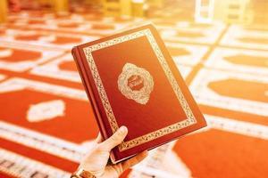 mão segurando Alcorão foto