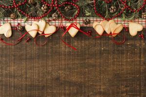 cookies de coração com ramos verdes e cones de borda de fundo foto