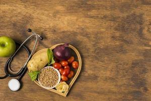 alimentos saudáveis e equipamentos médicos em fundo de madeira foto