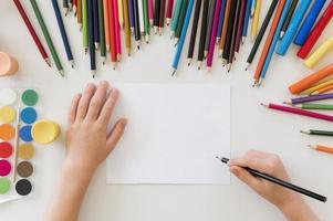 criança desenhando com lápis coloridos foto