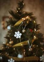 árvore de natal decorada com enfeites brancos dourados foto