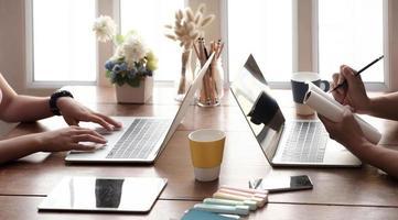 duas pessoas trabalhando juntas em uma mesa foto