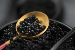 caviar preto em uma colher de ouro foto