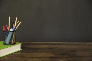 livro com copo de lápis e papelaria na mesa