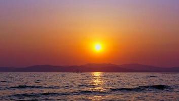colorido laranja pôr do sol sobre montanhas um corpo de água foto