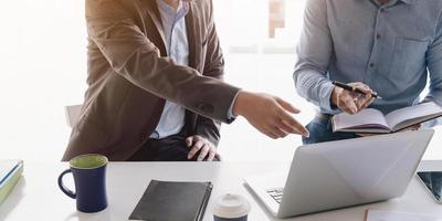 profissionais de negócios apontando para um laptop