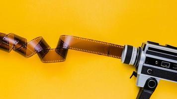 câmera de vídeo vintage e fita em fundo laranja foto