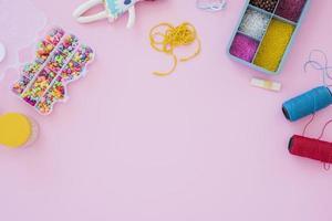 miçangas coloridas e caixa de carretéis de fios em fundo rosa foto