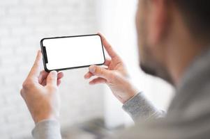 homem close-up segurando um smartphone foto