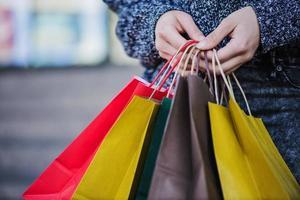 close-up das mãos de um comprador com sacolas foto