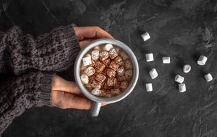 mãos segurando chocolate quente com marshmallows foto