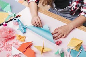 artista feminina dobrando papel de origami fazendo um belo artesanato foto