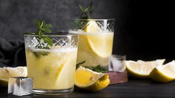Coquetel de bebida alcoólica com rodelas de limão em fundo escuro foto