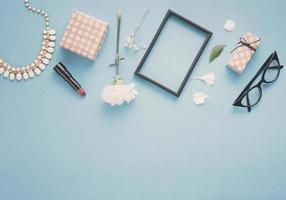 moldura em branco com flores, caixas de presente e batom em fundo azul foto