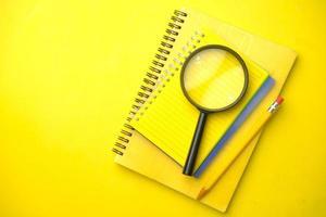 caderno amarelo e lápis com lupa foto