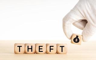 conceito de roubo a mão escolhendo um bloco de madeira com ícone de bolsa de dinheiro foto