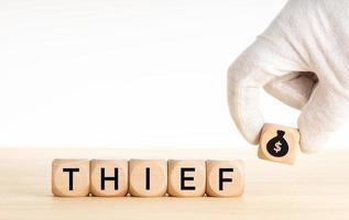 mão do conceito de ladrão escolhendo um ícone de bolsa de dinheiro foto