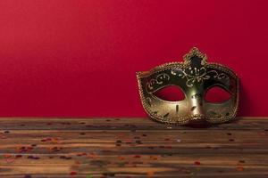 máscara de carnaval perto de parede vermelha foto
