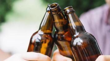amigos próximos a tilintar garrafas de cerveja castanhas foto