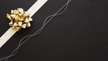 laço de fita decorativo e cordão de prata em fundo preto foto